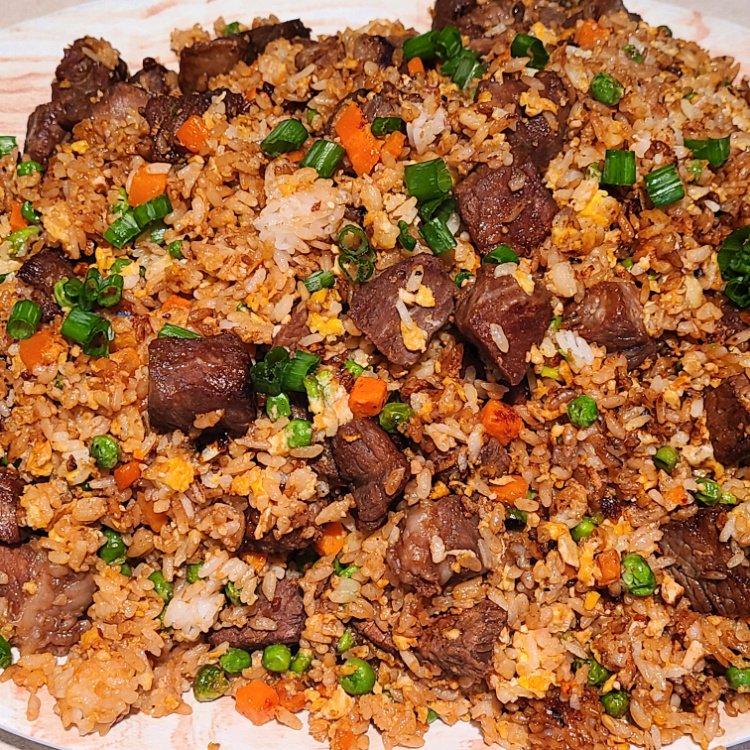 Teriyaki Steak Fried Rice On The Blackstone is the perfect weeknight dinner! Easy to make and the marinade makes for amazing flavor on the steak! Make on the Blackstone to keep the kitchen clean and quick clean up! Use frozen carrots and peas with a rice cooker for an easy dinner the whole family will eat! Cook this hibachi-style outside and look like a professional chef!