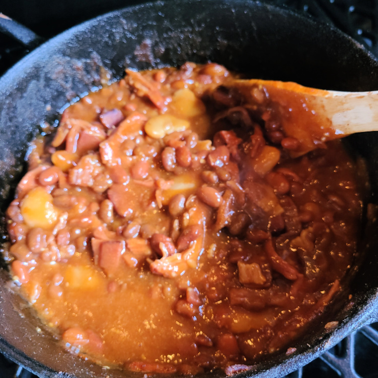 This Smoked Shredded Pork Baked Beans Recipe is the perfect side dish to use up leftover shredded pork! Plus it also makes a great lunch as well! Smoke these beans in a cast iron dutch oven to add more flavor to the beans as well! This is perfect to serve at a bbq or family get-together.